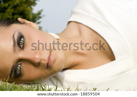 Adult woman with green eyes staring at the camera on a sunny day - stock photo