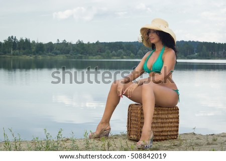 Adult woman with old brown suitcase relaxing to the water of a natural pond.