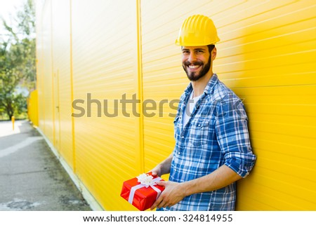 adult worker with yellow helmet and plaid shirt next to a wall smiling with a gift in hands