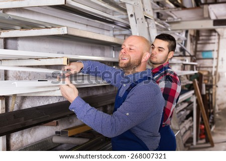 Adult workmen choosing PVC window profile at factory - stock photo