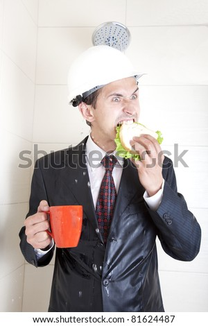 adult young businessman at breakfast in the shower in a business suit and helmet. eating sandwich and drinking from red cups - stock photo