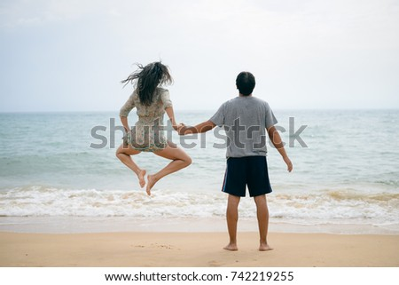 Adult young happy jumping couple on seashore outdoors nature sand background. Back view of pretty romantic lovers having fun holding hands in tenderness bliss moment. destination trip