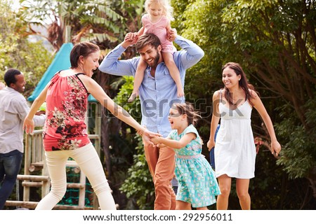 Adults and kids having fun playing in a garden - stock photo