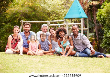 Adults and kids sitting on grass in a garden, group portrait - stock photo