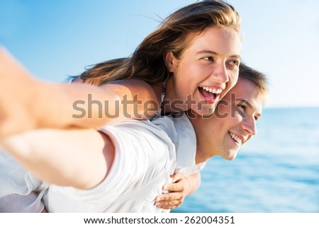 Adults. Beach couple laughing in love romance on travel honeymoon vacation summer holidays romance. Young happy people, Asian woman and Caucasian man embracing outdoors on tropical beach in casual - stock photo