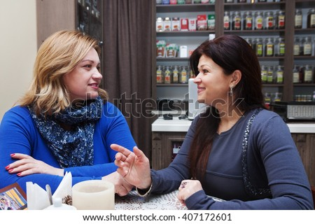 Adults girlfriends communicate in retro cafe
