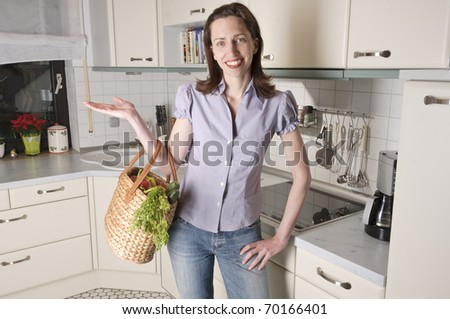Adults Only woman with a basket full of fresh vegetables in their kitchen bright and smiling at the camera. - stock photo