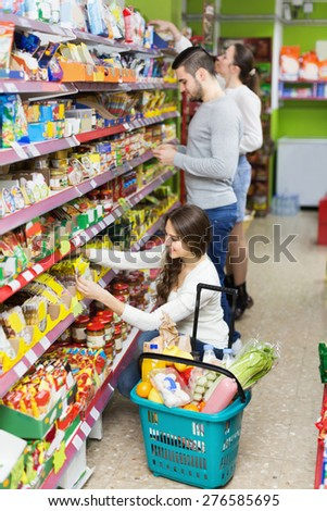 Adults people standing near shelves with canned goods at shop
