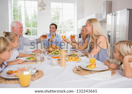 Adults raising their glasses at thanksgiving dinner without children