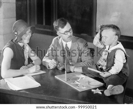 Adults testing little boy doing puzzle - stock photo