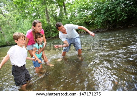 Adults with kids throwing pebbles in river - stock photo