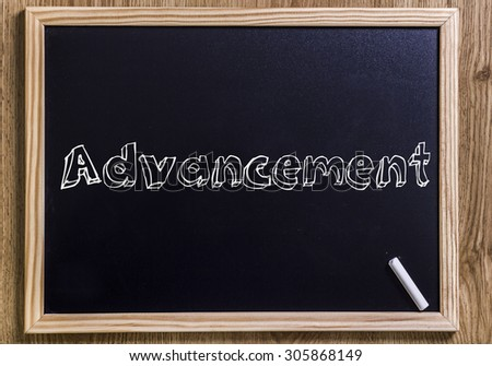 Advancement - New chalkboard with outlined text - on wood - stock photo