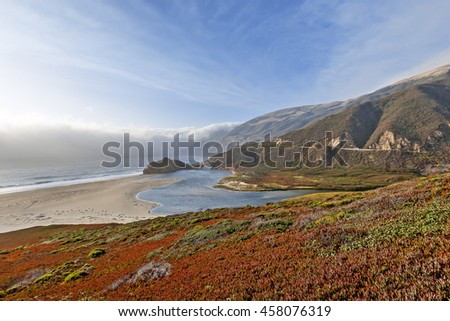 Advancing storm front, waves splashing on huge rocks, off shore, along a rocky coastline, at the inlet to the Little Sur River, traveling the Big Sur Highway (Highway 1), California Central Coast. - stock photo