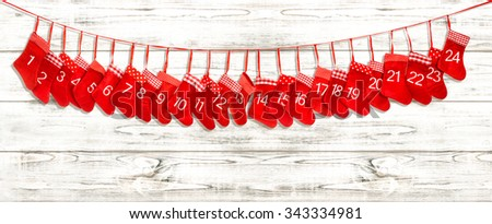 Advent calendar 1-24. Christmas decoration red stocking on bright wooden background - stock photo