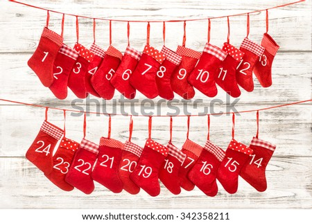 Advent calendar 1-24. Christmas decoration red stocking over wooden background - stock photo