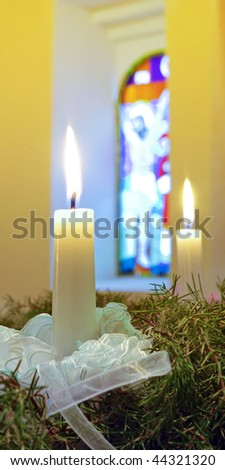 advent candles on the wreath against stained-glass window - stock photo