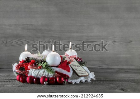 Advent crown with three candles in red and white on grey wooden background. - stock photo