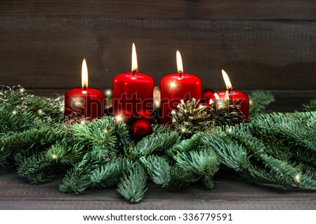Advent decoration wreath with four red burning candles and light effects. Holidays background. selective focus - stock photo
