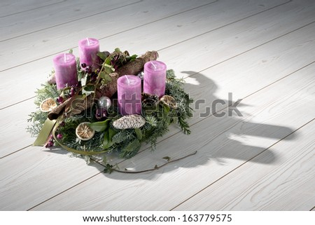 Advent wreath of twigs with purple candles and various ornaments - stock photo