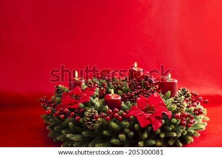 Advent wreath over red background with winter rose and berries - stock photo