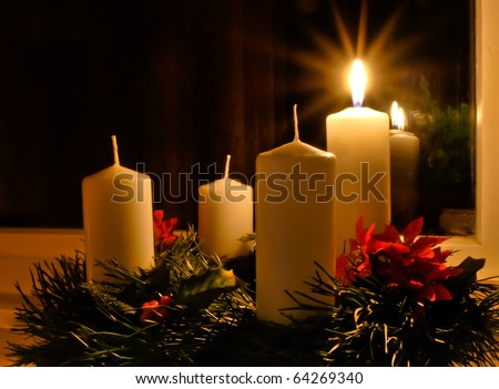 Advent wreath with a lighted candle placed on the window - stock photo