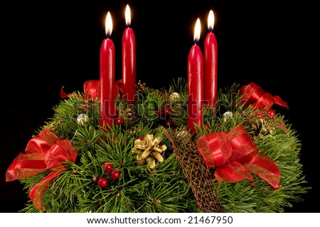 Advent wreath with red candles, four candles with flame. Isolated on black background. - stock photo