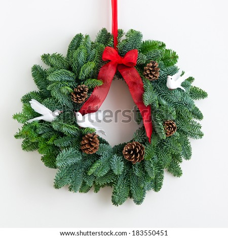 Advent wreath with red ribbon over bright wall
