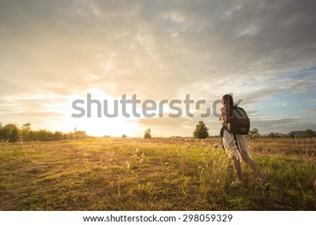 Adventure alone into the meadow at sunset. - stock photo