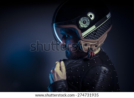 Adventure, biker with motorcycle helmet and black leather jacket, metal studs - stock photo