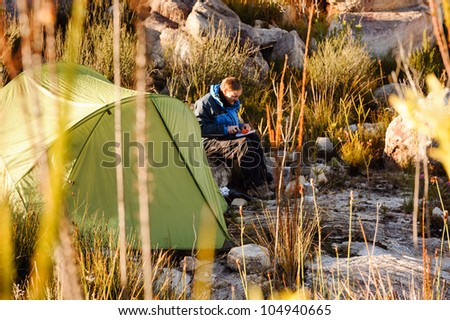 Adventure camping man cooking alone outdoors with tent, sunrise and lens flare in the mountain morning sunlight. Happy explorer enjoying a meal in the wilderness - stock photo