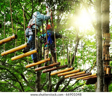 adventure climbing high wire park - people on course in mountain helmet and safety equipment - stock photo