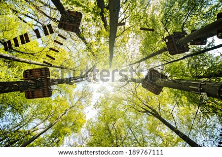 adventure climbing high wire park with the sun in the trees - stock photo