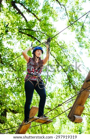 Adventure climbing high wire park - woman on course in mountain helmet and safety equipment - stock photo