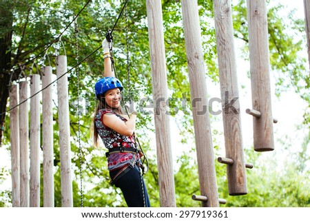 Adventure climbing high wire park - woman on course in mountain helmet and safety equipment