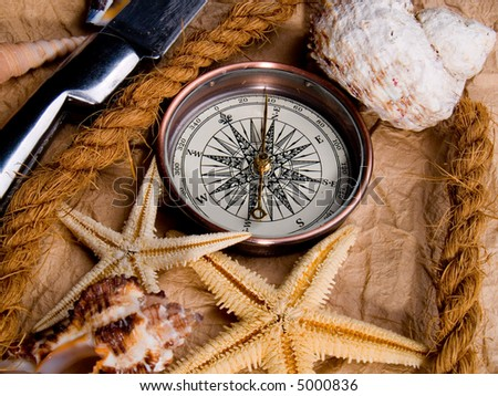 Adventure decoration with compass and shells on antique parchment. - stock photo