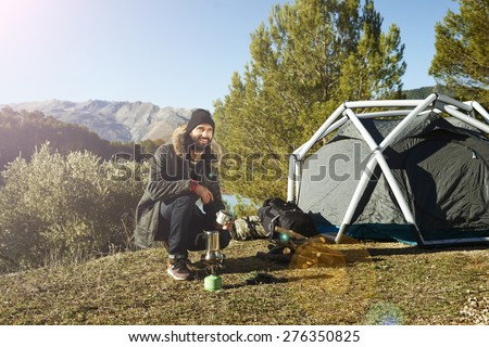 Adventure hiking man with coffee and backpack relaxing after outdoor activity.  Hikers sitting in grass near tent smiling happy outdoors in mountain forest enjoying sun. Conceptual scene.  - stock photo