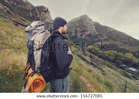 Adventure man hiking wilderness mountain with backpack, outdoor lifestyle survival vacation - stock photo