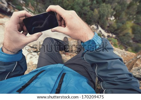 Adventure man with gps device or phone outdoors in wilderness exploring - stock photo