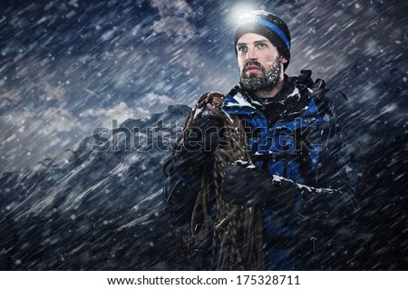 adventure mountain man in snow blizzard looking on with determination and courage - stock photo
