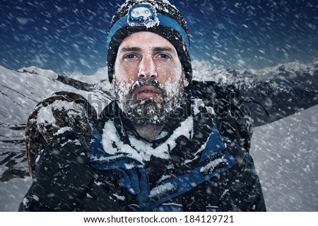 Adventure mountain man in snow expedition with climbing gear and determination - stock photo