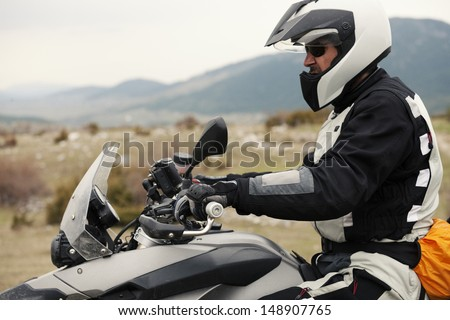 Adventure rider traveling, outdoor shot. Strong grain. - stock photo