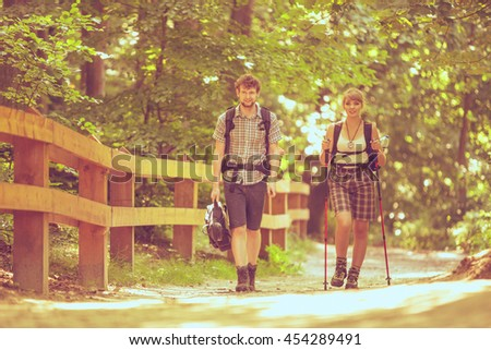 Adventure, tourism active lifestyle- young couple backpacker hiking in forest pathway - stock photo
