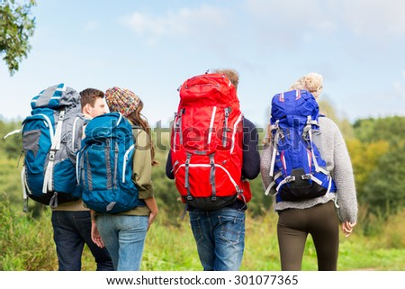 adventure, travel, tourism, hike and people concept - group of friends walking with backpacks from back - stock photo