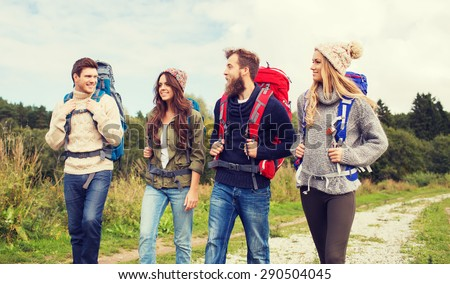 adventure, travel, tourism, hike and people concept - group of smiling friends walking with backpacks - stock photo