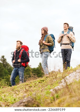 adventure, travel, tourism, hike and people concept - group of smiling friends with backpacks outdoors - stock photo