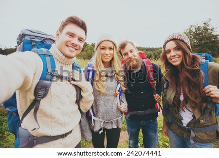 adventure, travel, tourism, hike and people concept - group of smiling friends with backpacks making selfie outdoors - stock photo