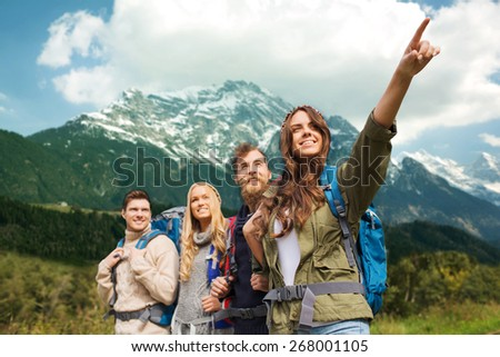 adventure, travel, tourism, hike and people concept - group of smiling friends with backpacks pointing finger over alpine mountains background - stock photo