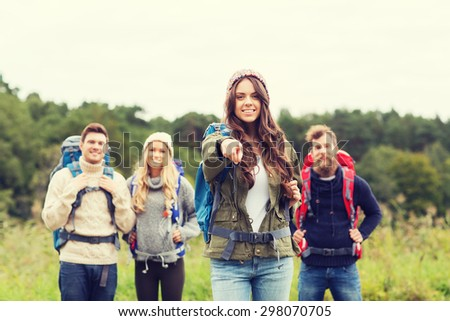 adventure, travel, tourism, hike and people concept - group of smiling friends with backpacks pointing finger outdoors - stock photo