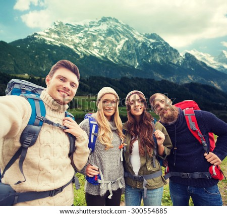 adventure, travel, tourism, hike and people concept - group of smiling friends with backpacks making selfie over alpine mountains background - stock photo
