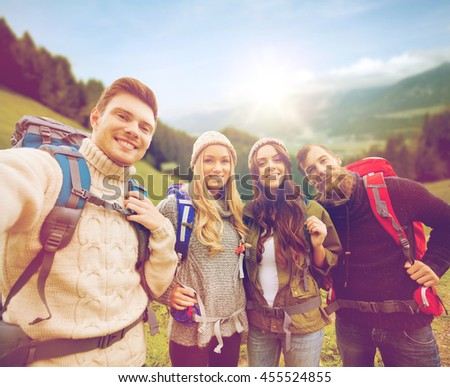 adventure, travel, tourism, hike and people concept - group of smiling friends with backpacks making selfie over alpine mountains and hills background - stock photo